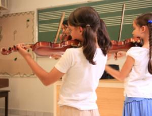 Two girls with pigtails playing violin in a classroom. They are facing away from the camera.